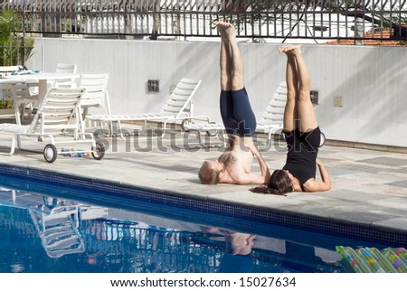 A man and a woman are exercising together beside a pool.  They are on the ground with their legs and torsos in the air.  They are looking away from camera.  Horizontally framed photo.