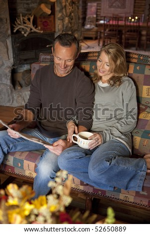 A man and a woman are smiling and sitting on a couch reading a newspaper. The woman is holding a coffee cup. Vertical shot.