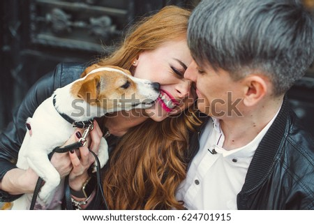A man and a woman are walking around the city.They are holding a dog. Jack is scattered in his arms