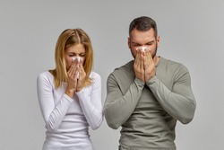 A man and a woman blow their nose in a napkin on an isolated white background. Portrait of people with cloth in their hands. The concept of treating allergies or colds.