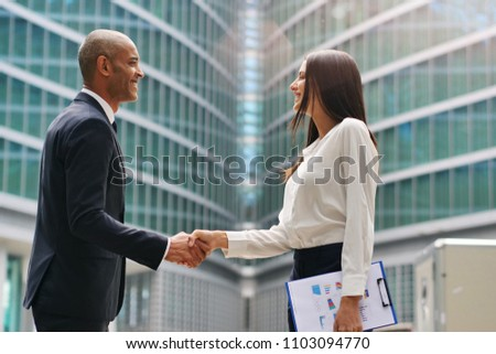 A man and a woman business, of different ethnicities, shake hands and then talk about finance looking at the patterns of economic markets and banks. Concept of: success and team #1103094770