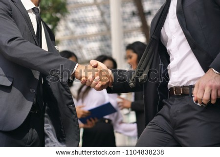 A man and a woman business, of different ethnicities, shake hands and then talk about finance looking at the patterns of economic markets and banks. Concept of: success and team #1104838238