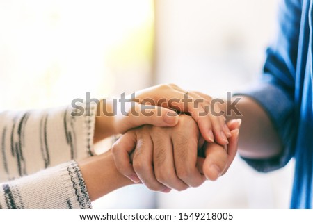 A man and a woman holding each other hands for comfort and sympathy Foto stock ©