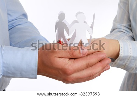 A man and a woman holding paper people, close-up, isolated on white