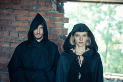 a man and a woman in black raincoats