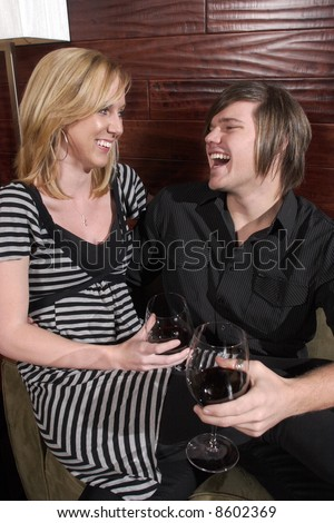 A man and a woman laugh at a wine lounge