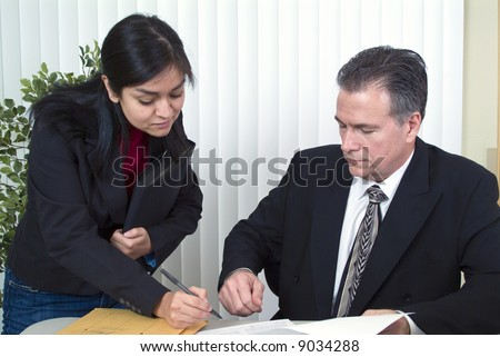 A man and a woman looking at a document that the woman is about to sign.