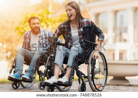 A man and a woman on wheelchairs ride around the park. They arranged a race in wheelchairs. On a background of a beautiful green park. Photo stock ©