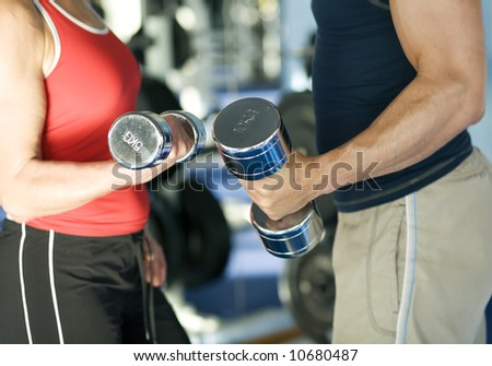 A man and a woman (only arms and body) lifting dumbbells (shallow depth of field, focus only on hands)