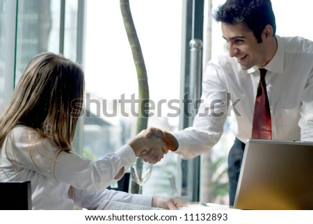 A man and a woman shaking hands on a business deal.
