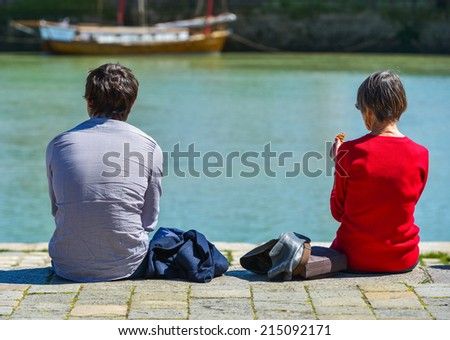 A man and a woman sitting at the pier and looking at the sea with the blury view of a ship in the background #215092171