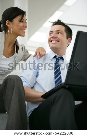 A man and a woman sitting in front of a laptop