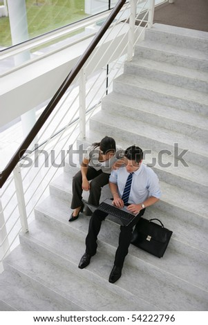 A man and a woman sitting on the steps of a staircase in front of a laptop