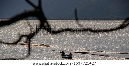 A man and a women driving a boat with paddle at lake during sundown.