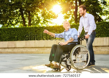 A man and an old man are walking in the park. The old man is sitting in a wheelchair. The man is carrying it