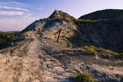 A man and dog hike across Devil's Pass in late afternoon light. Maah Daah Hey Trail, North Dakota.
