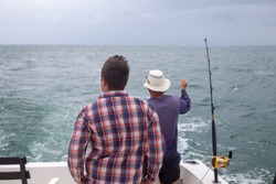 A man and fishing guide checks his fishing rods on a charter boat in Varadero, Cuba on a day excursion deep sea fishing in the Caribbean Ocean