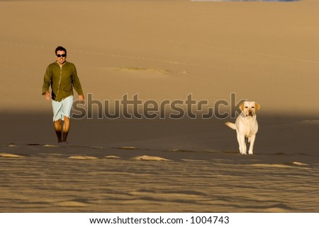 A man and his dog taking a walk on the dunes.