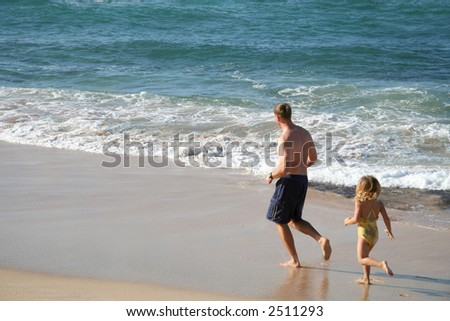 A man and his young daughter running along the beach