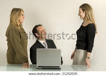 A man and two women in an office setting.  They are smiling and facing one another. Horizontally framed shot.