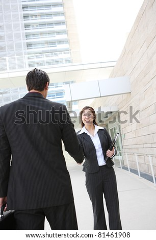 A man and woman business team shaking hands at office building