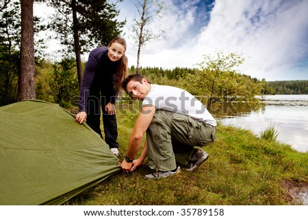 A man and woman camping - setting up a tent