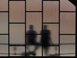 a man and woman couple sitting on a bench behind glass opaque windows , sitting couple seen through an opaque glass, close to each other