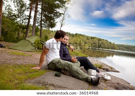 A man and woman happy camping in the forest by a lake