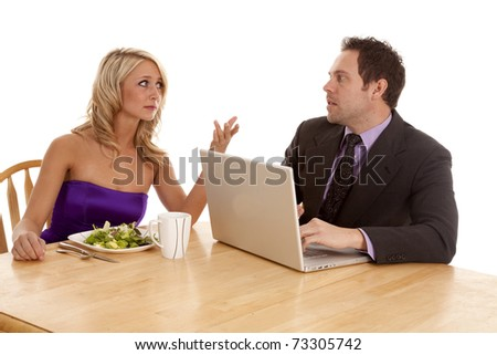 A man and woman looking at each other with unhappy expressions on their faces because the man is working on his computer at dinner.