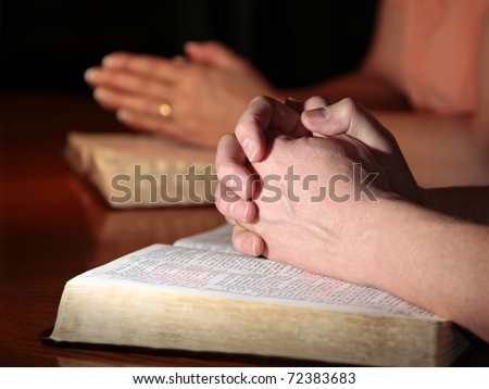 A man and woman (or couple) praying together at a table with their Holy Bibles open under their hands (focus on man's foreground hands).
