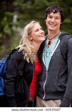 A man and woman outdoors on a hike in a forest