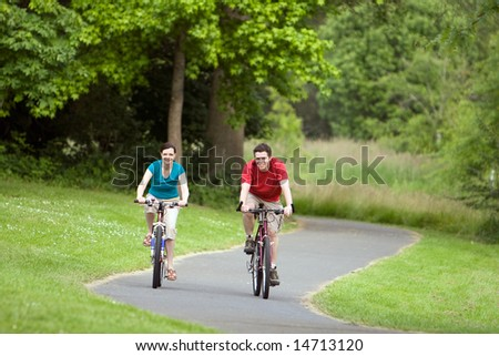 A man and woman, ride their bicycles along a park trail happily. - horizontally framed