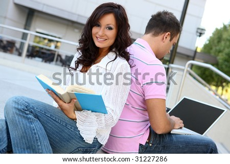 A man and woman student at school studying outside library