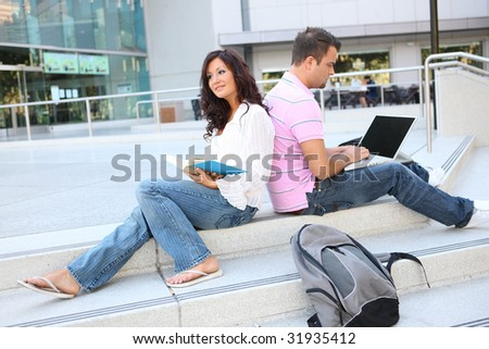 A man and woman student at school studying outside library - stock photo