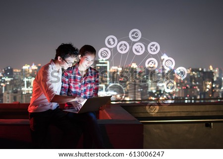 A man and woman using laptop with IOT, internet of things conceptual sign, internet era, internet in every day lifes