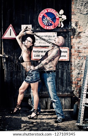 A man and woman with a lot of tattoos at a junkyard