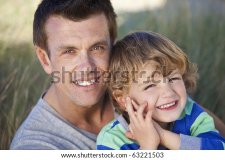 A man and young boy, father and son, sitting down and having fun in the grassy sand dunes of a sunny beach