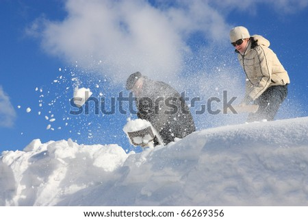 A man and young woman removing snow from a roof