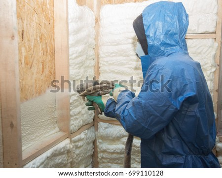 A man applies an insulating foam to the wall of the house #699110128