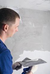 a man applies mortar to a trowel before repairing a wall