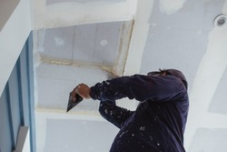 A man applies putty to a ceiling of an almost complete home. Wearing clothes full of paint splotches. Shot at the garage area.