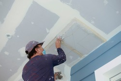 A man applies putty to gypsum ceiling of an almost complete home. Wearing clothes full of paint splotches. Shot at the garage area.