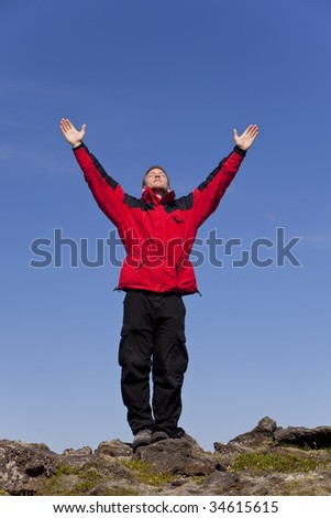 A man arms outstretched celebrating success at the top of a mountain.