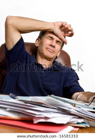 A man at his desk worrying how he will pay the bills