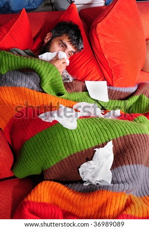 A man at home with the flu. He's wrapped up in a blanket on the couch with his cat and tissue paper.