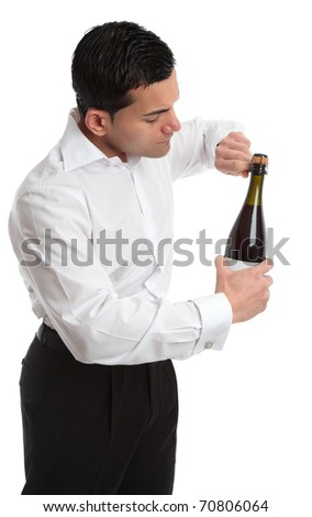 A man, bartender or waiter opens a bottle of champagne, sparkling wine.  He is untwisting the metal cage around the cork.  Sideview.   White background.