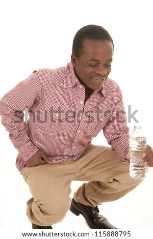 A man bending down with a bottle of water with a smile on his face. - stock photo