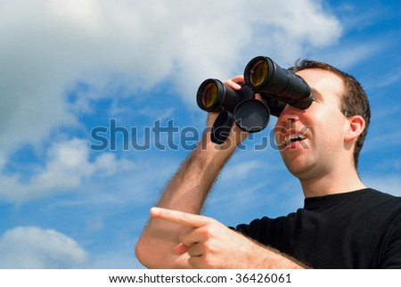 A man bird watching with a set of binoculars and is pointing with his finger