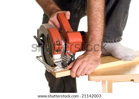 A man bracing a piece of wood with his foot in order to cut a piece of lumber with a skilsaw