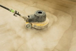 A man builder grinds a concrete floor with a sander in a warehouse